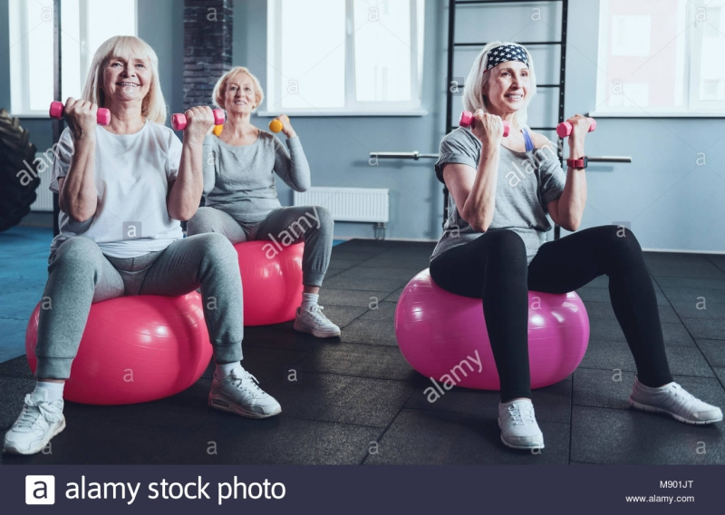 Original source: https://c8.alamy.com/comp/M901JT/senior-women-exercising-with-dumbbells-on-fitness-ball-in-gym-M901JT.jpg